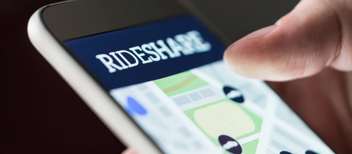Ride share app in smartphone. Man using rideshare taxi application. Online carpool or carsharing service in mobile phone. Macro close up of cellphone screen.