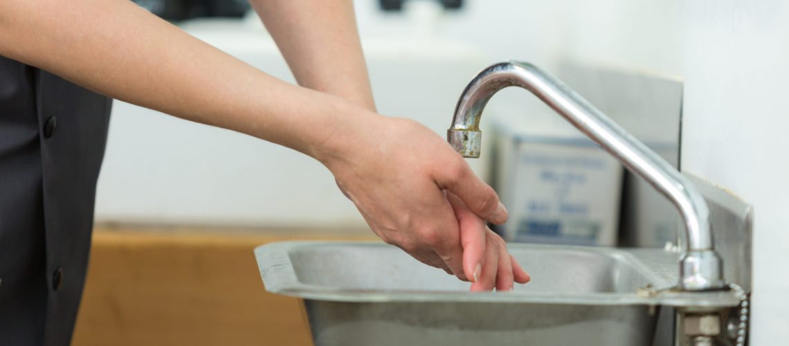 professional washing hands in stainless steel sink