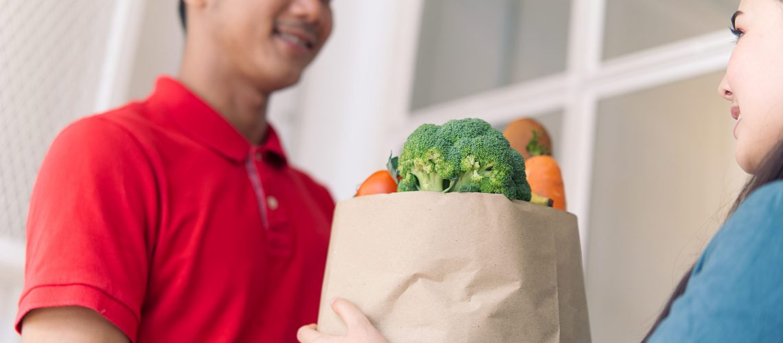 Asian delivery man in red color uniform handling bag of foods or vegetables to young beautiful female costumer in front of the house. Postman or express delivery service concept. Focus on girl eyes.