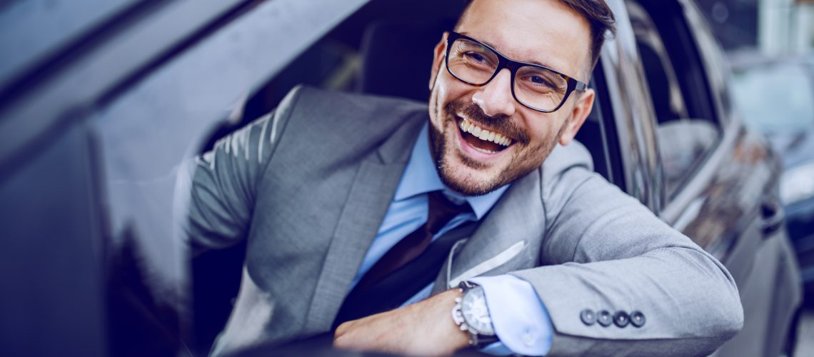 Smiling businessman looking trough window while driving his expensive car. Business trip concept.